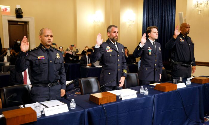 (L-R) U.S. Capitol Police Sergeant Aquilino Gonell, DC Metropolitan Police Department Officer Michael Fanone, DC Metropolitan Police Department Officer Daniel Hodges, and US Capitol Police Private First Class Harry Dunn, are sworn in before members of the Select Committee to Investigate the January 6th Attack on the U.S. Capitol during their first hearing on Capitol Hill in Washington, on July 27, 2021. (Jim Bourg/Pool/AFP via Getty Images)
