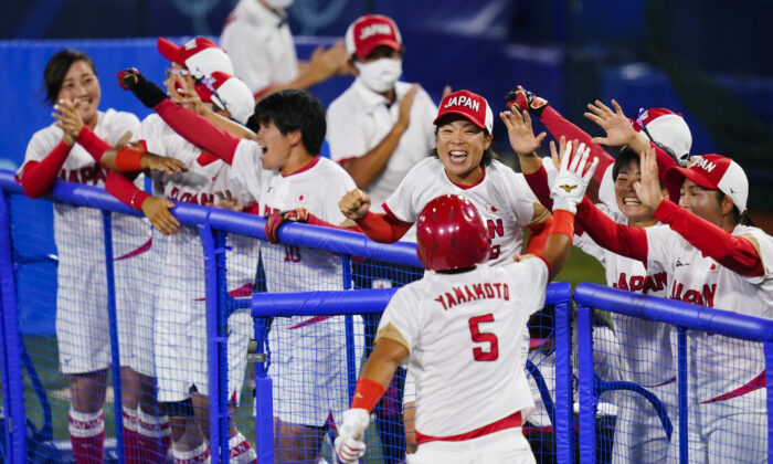 Japan's Yu Yamamoto (5) celebrate with teammates after scoring on a single in the fifth inning of a softball game against the United States at the 2020 Summer Olympics, in Yokohama, Japan, on July 27, 2021. (Matt Slocum/AP Photo)