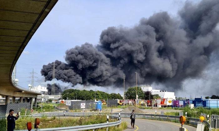 A dark cloud of smoke rises above the chemical park in Leverkusen, Germany, on July 27, 2021. (Mirko Wolf/dpa via AP)