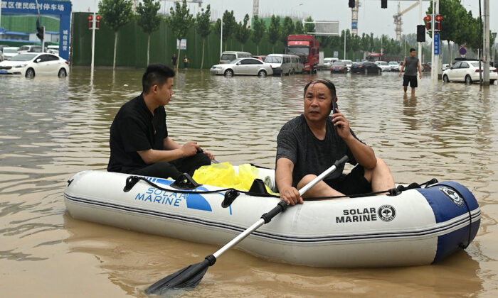 People uses a rubber dinghy to cross a flooded street following flooding that claimed the lives of at least 33 people earlier in the week, in the city of Zhengzhou in China's Henan province on July 23, 2021. (Noel Celis/AFP via Getty Images)