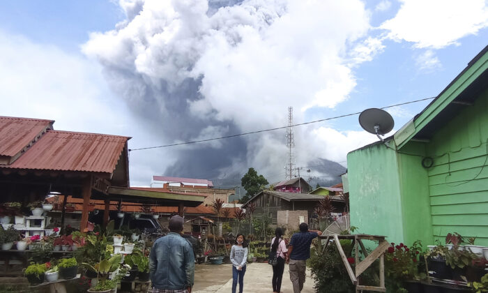 People watch as Mount Sinabung spews volcanic materials during an eruption in Karo, North Sumatra, Indonesia on Wednesday, July 28, 2021. (Sastrawan Ginting/AP Photo)