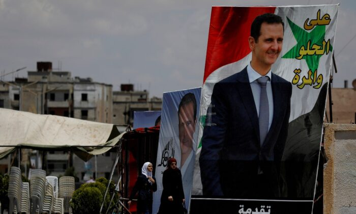 People walk past posters depciting Syria's President Bashar al-Assad, ahead of the May 26 presidential election, in the district of al-Waer in Homs, Syria, on May 23, 2021. (Omar Sanadiki/Reuters)
