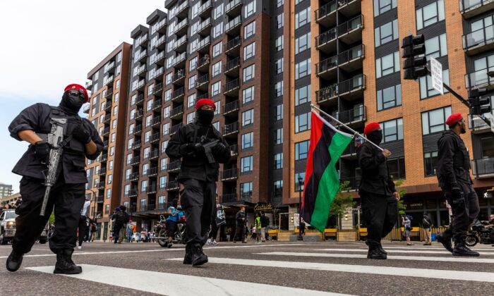 """An armed group calling themselves """"The Originals of the Minneapolis Black Panthers"""" marches with other protesters during an event in remembrance of George Floyd in Minneapolis, Minn., on May 23, 2021. (Kerem Yucel/AFP via Getty Images)"""