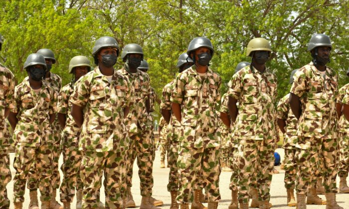 Soldiers stand on guard during Nigerian President Muhammadu Buhari's visit to the Maimalari Barracks in Maiduguri, Nigeria on June 17, 2021. (Audu Marte/AFP via Getty Images)