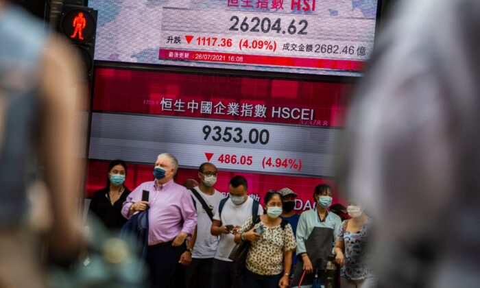 People stand in front of an electronic display showing the Hang Seng Index in the Central district of Hong Kong on July 26, 2021. (Isaac Lawrence/AFP via Getty Images)