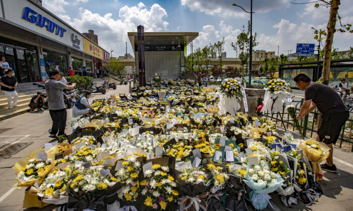 A man places flowers with other bouquets in front of a subway station in memory of flood victims in Zhengzhou, central China's Henan Province, on July 27, 2021. (STR/AFP via Getty Images)