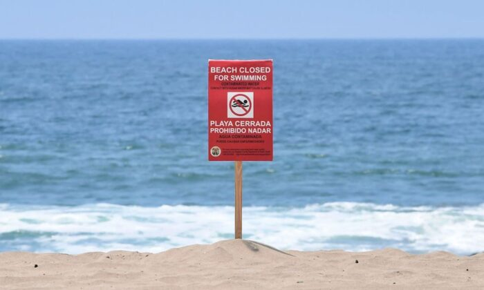 A sign indicates that the Dockweiler State Beach is closed to swimming after a sewage spill in Playa del Rey in Los Angeles County on July 13, 2021. (Frederic J. Brown/AFP Via Getty Images)