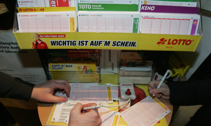 People fill out Lotto tickets in Germany in a file photo. (John Macdougall/AFP via Getty Images)