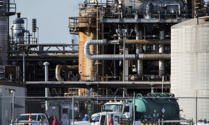Workers stand in a lot at a LyondellBasell facility in La Porte, Texas, on July 27, 2021. (Mark Mulligan/Houston Chronicle via AP)