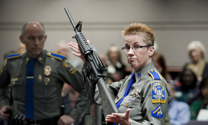 Firearms training unit Detective Barbara J. Mattson, of the Connecticut State Police, holds up a Bushmaster AR-15 rifle, the same make and model of gun used by Adam Lanza in the Sandy Hook School shooting, for a demonstration during a hearing of a legislative subcommittee reviewing gun laws, at the Legislative Office Building in Hartford, Conn., on Jan. 28, 2013. (Jessica Hill/AP Photo)
