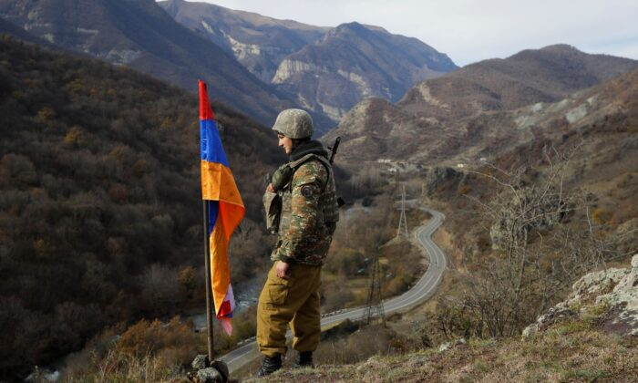 An ethnic Armenian soldier stands guard next to Nagorno-Karabakh's flag atop of the hill near Charektar in the separatist region of Nagorno-Karabakh at a new border with Kalbajar district turned over to Azerbaijan, on Nov. 25, 2020. (Sergei Grits/File/AP Photo)