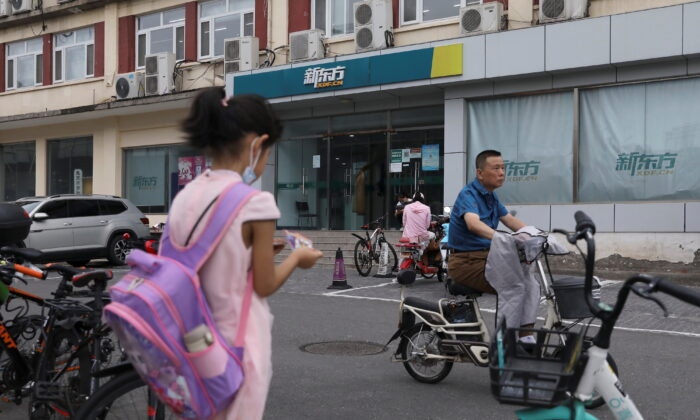 A girl carrying a schoolbag stands near an outlet of private educational services provider New Oriental Education and Technology Group in Beijing, China, on July 26, 2021. (Tingshu Wang/Reuters)