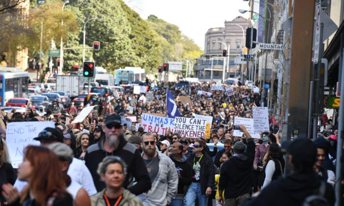 """Protesters march along Broadway and George St toward Sydney Town Hall during the """"World Wide Rally For Freedom"""" anti-lockdown rally at Hyde Park in Sydney, Australia, on July 24, 2021. (Mick Tsikas/AAP Image)"""