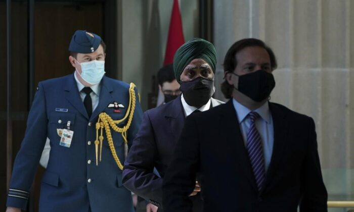 Immigration Minister Marco Mendicino, right, is joined by Harjit Sajjan, Minister of National Defence, second from right, as they arrive for a press conference in Ottawa on July 23, 2021. (The Canadian Press)