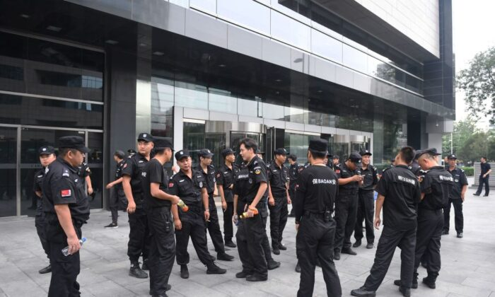 Security personnel stand in front an entrance to China's Banking Regulatory Commission in Beijing on Aug. 6, 2018. (Greg Baker/ AFP/via Getty Images)
