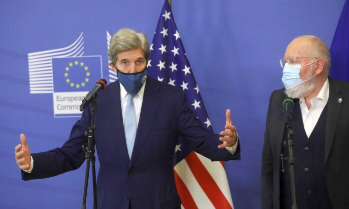 European Commission vice-president in charge for European green deal Frans Timmermans (R) welcomes U.S. Special Presidential Envoy for Climate John Kerry prior to a meeting in Brussels, on March 9, 2021. (Olivier Hoslet/Pool/AFP via Getty Images)