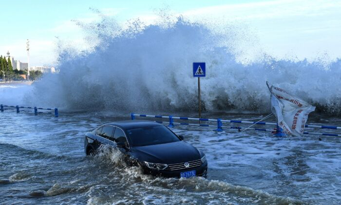 A car sits in flood waters as waves, caused by Typhoon In-fa, surge over a barrier along the seacoast in China's eastern Shandong Province, on July 25, 2021. (STR / AFP)