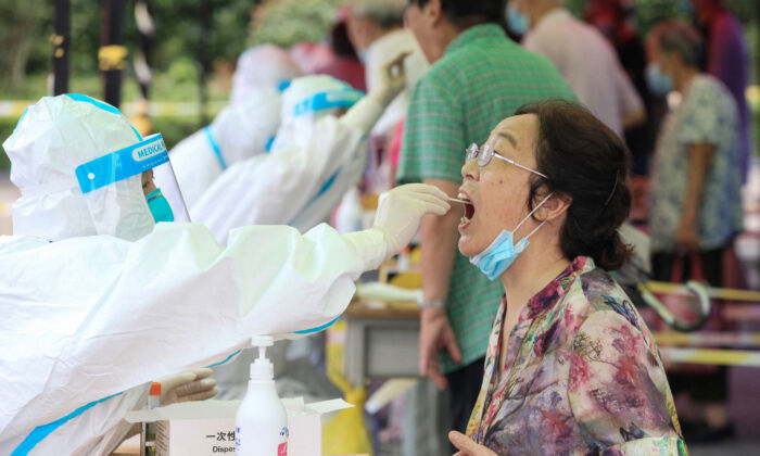 A woman receives a test for the COVID-19 in Nanjing, eastern China's Jiangsu Province on July 29, 2021. (STR/AFP via Getty Images)