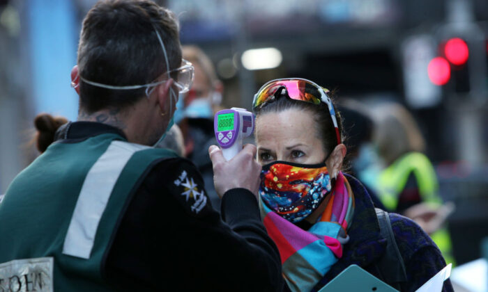 A St John Ambulance staff member takes the temperature of a client arriving at a COVID-19 Vaccination Centre in the CBD in Sydney, Australia on July 19, 2021. (Lisa Maree Williams/Getty Images)