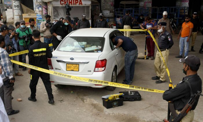 Investigators examine a damaged car at the site of a firing incident, in Karachi, Pakistan, on July 28, 2021. (Fareed Khan/AP)