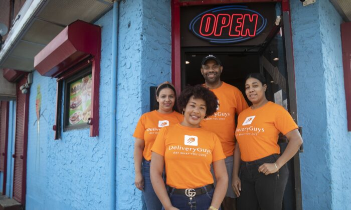 From left, clockwise, Lorainy Espinal, Victor Tejada, Nathalie Zapata, and Katty Dorporan pose for a portrait outside Sabor Rico Bakery in North Philadelphia. (Heather Khalifa/The Philadelphia Inquirer/TNS)