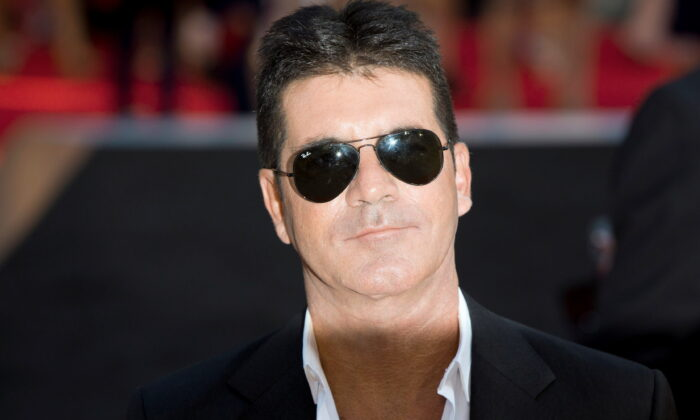 """Television mogul Simon Cowell poses for photographers as he arrives for the film """"One Direction: This is Us,"""" in London, England, on Aug. 20, 2013. (Neil Hall/Reuters)"""