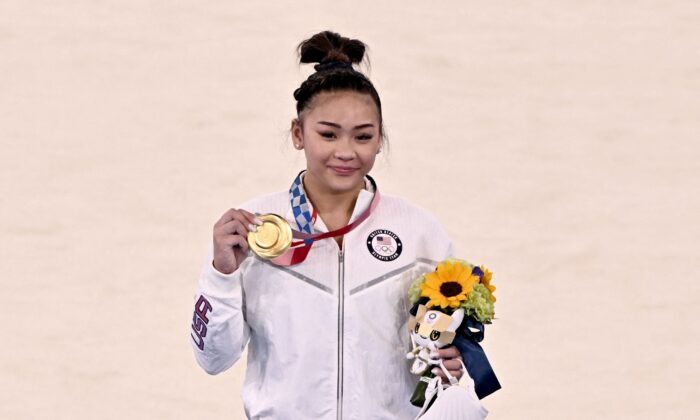Sunisa Lee of the United States (gold) celebrates on the podium during the medal ceremony of the artistic gymnastics women's all-around final during the Tokyo 2020 Olympic Games at the Ariake Gymnastics Centre in Tokyo, Japan, on July 29, 2021. (Lionel Bonaventure/AFP via Getty Images)