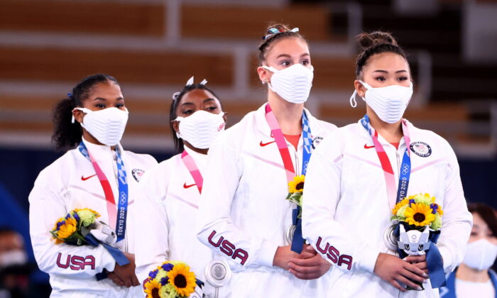 Jordan Chiles, Simone Biles, Grace McCallum, and Sunisa Lee of Team United States react on the podium after winning the silver medal during the Women's Gymnastics Team Final on day four of the Tokyo 2020 Olympic Games at Ariake Gymnastics Centre in Tokyo, Japan, on July 27, 2021. (Lindsey Wasson/Reuters)