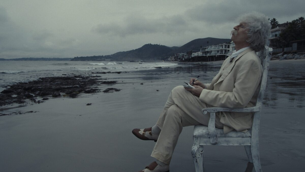 man in white suit on beach in Val