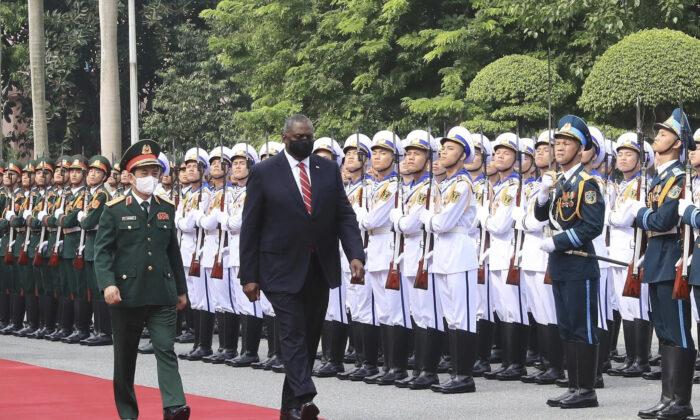 U.S. Secretary of Defense Lloyd Austin (R) with Vietnamese Defense Minister Phan Van Giang (L) inspects an honor guard in Hanoi, Vietnam, on July 29, 2021. (Nguyen Trong Duc/VNA via AP)