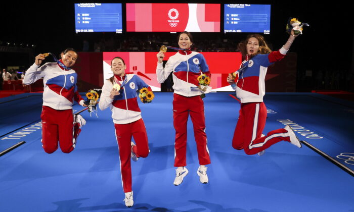 Gold medalists Inna Deriglazova, Adelina Zagidullina, Larisa Korobeynikova, and Marta Martyanova of the ROC celebrate their victory during the medal ceremony for the women's foil team at the Tokyo 2020 Olympic Games at the Makuhari Messe Hall in Chiba City, Chiba Prefecture, Japan, on July 29, 2021. (Carl Recine/Reuters)
