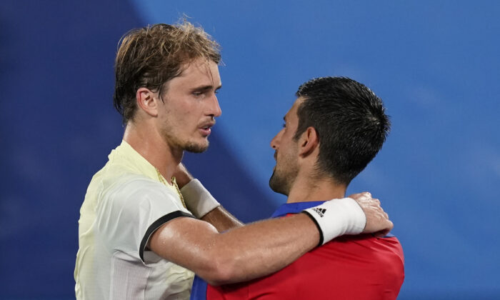 Alexander Zverev (L) of Germany, speaks with Novak Djokovic, of Serbia, after defeating Djokovic in the semifinal round of the men's tennis competition at the 2020 Summer Olympics in Tokyo, Japan, on July 30, 2021. (Patrick Semansky/AP Photo)