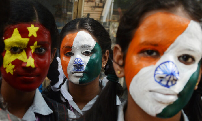 Indian school students pose with their faces painted with India's and China's (L) national flags in Chennai on October 10, 2019, ahead of a summit between Indian PM, Narendra Modi and China's leader Xi Jinping in the Indian city of Chennai. (Arun Sankar/AFP via Getty Images)