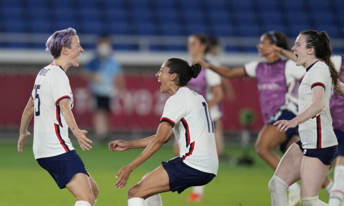 United States' Megan Rapinoe (L) celebrates with teammates after scoring the winning goal and defeating the Netherlands in a penalty shootout during a women's quarterfinal soccer match at the 2020 Summer Olympics in Yokohama, Japan, on July 30, 2021. (Silvia Izquierdo/AP Photo)