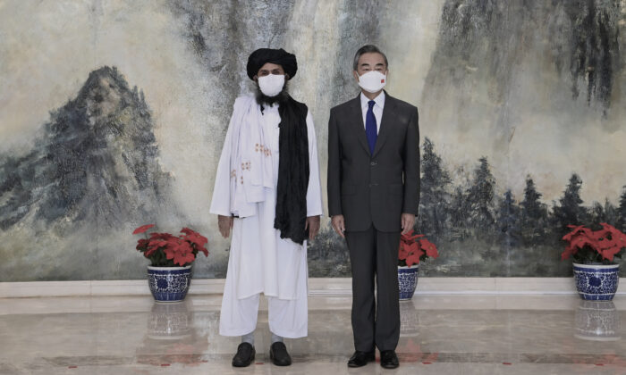 Taliban co-founder Mullah Abdul Ghani Baradar (L) and Chinese Foreign Minister Wang Yi pose for a photo during their meeting in Tianjin, China, on July 28, 2021. (Li Ran/Xinhua via AP)