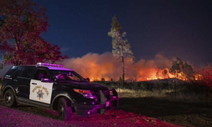 A California Highway Patrol officer watches flames that are visible from the Zogg Fire on Clear Creek Road near Igo, Calif., on Sep. 28, 2020. (Ethan Swope/AP Photo)