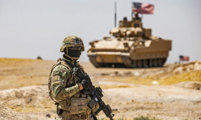 A U.S. soldier stands near a Bradley Fighting Vehicle (BFV) during a patrol near the Rumaylan (Rmeilan) oil wells in Syria's northeastern Hasakeh province on June 22, 2021. (Delil Soulieman/AFP via Getty Images)