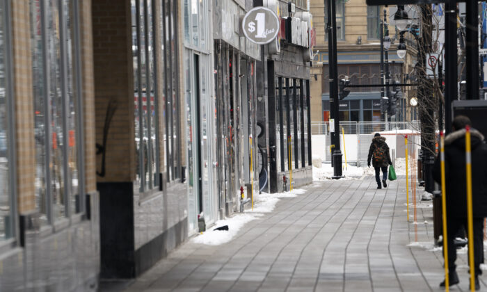 A man walks down a quiet Saint-Catherine Street under Quebec's new COVID-19 lockdown, in Montreal on Jan. 11, 2021. (The Canadian Press/Paul Chiasson)
