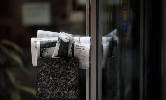 Newspapers are stuffed into a door handle of a closed building during morning commuting hours in Toronto on April 1, 2020. (Cole Burston/Getty Images)