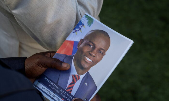 A person holds a photo of late Haitian President Jovenel Moise, who was shot dead in early July, during his funeral at his family home in Cap-Haitien, Haiti, on July 23, 2021. (Ricardo Arduengo/Reuters)