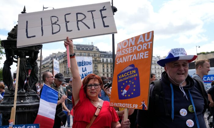 """A protestor holds a sign which reads in French """"freedom"""" and """"no to the Covid passport"""" as she attends a demonstration in Paris on July 31, 2021. (Michel Euler /AP Photo)"""