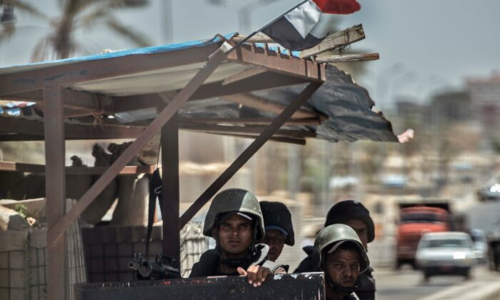 Egyptian policemen stand guarding a checkpoint on a road leading to the North Sinai provincial capital of El-Arish in a file photo. (Khaled Desouki/AFP via Getty Images)