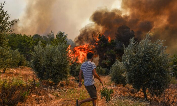 A man walks toward wildfires in Kacarlar village near the Mediterranean coastal town of Manavgat, Antalya, Turkey, on July 31, 2021. (AP Photo)