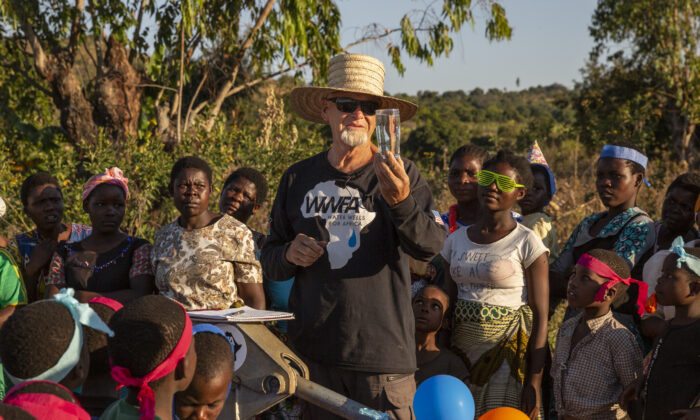 Water Wells or Africa founder Kurt Dahlin tests the water with Juma 2B villagers on July 2, 2021. (John Fredricks/The Epoch Times)