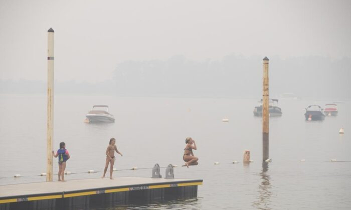 Wildfire smoke fills the air and obstructs the view of the mountains as people continue to take part in outdoor activities in Sicamous B.C., on July 29, 2021. (The Canada Press/Jason Franson)