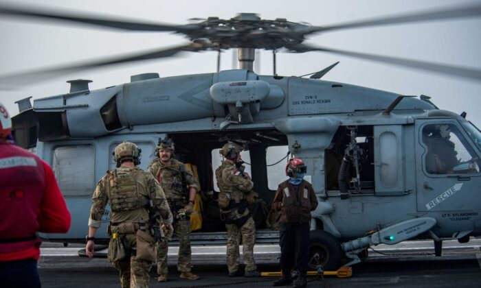 """Sailors assigned to Explosive Ordnance Disposal Mobile Unit (EODMU) 5 board an MH-60S Sea Hawk helicopter, attached to the """"Golden Falcons"""" of Helicopter Sea Combat Squadron (HSC) 12, are seen on the flight deck of aircraft carrier USS Ronald Reagan (CVN 76), in response to a call for assistance from the Mercer Street, a Japanese-owned Liberian-flagged tanker managed by Israeli-owned Zodiac Maritime, in the Arabian Sea, on July 30, 2021. (U.S. Navy/Handout via Reuters)"""
