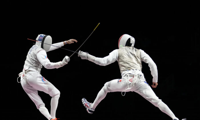 Anton Borodachev of the Russian Olympic Committee, left, and Erwann Le Pechoux of France compete in the men's Foil team final at the 2020 Summer Olympics, in Chiba, Japan, on Aug. 1, 2021. (Andrew Medichini/AP Photo)