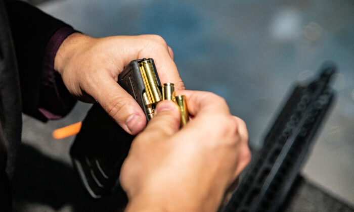 A man load .223 bullets into an AR-15 assault rifle at FT3 tactical shooting range in Stanton, Calif., on May 3, 2021. (John Fredricks/The Epoch Times)