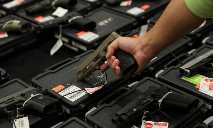 A potential buyer handles a gun that is displayed on an exhibitor's table during the Nation's Gun Show at Dulles Expo Center in Chantilly, Va., on Nov. 18, 2016. (Alex Wong/Getty Images)
