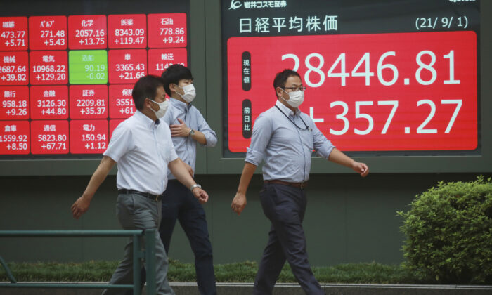 People walk by an electronic stock board of a securities firm in Tokyo, Japan, on Sept. 1, 2021.  (Koji Sasahara/AP Photo)